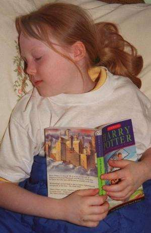A young girl falls asleep reading a Harry Potter book in London on July 7, 2000