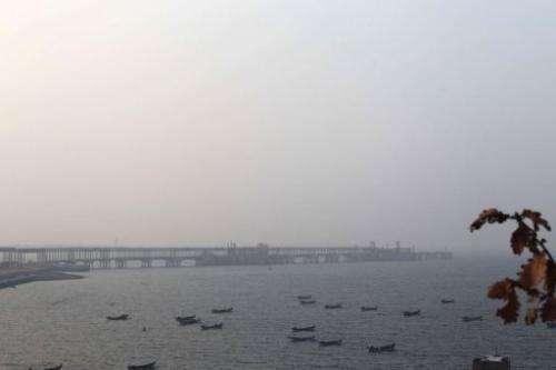 Boats berth in the waters near the Dalian Fujia Dahua Petrochemical factory in Dalian, China on January 18, 2013