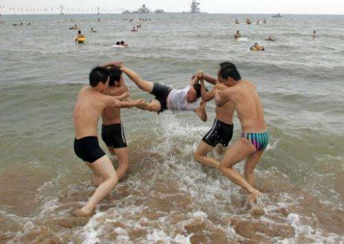 Boys toss a girl into the waters of the Bohai Sea at a beach in Qinhuangdao, on July 31, 2007
