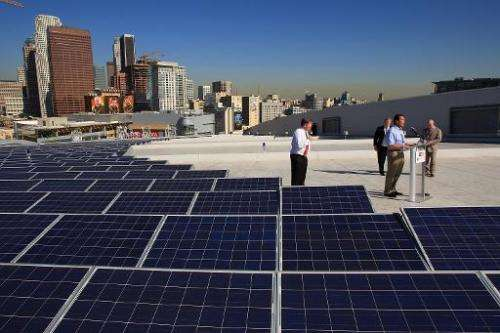 California Governor Arnold Schwarzenegger speaks at the installation the last of 1,727 solar panels on the rooftop of the Staple