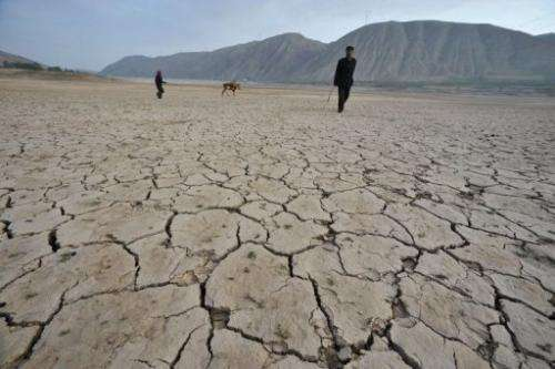 Chinese herders walk on a dried-up reservoir in Gulang, northern China's Gansu province on July 15, 2009
