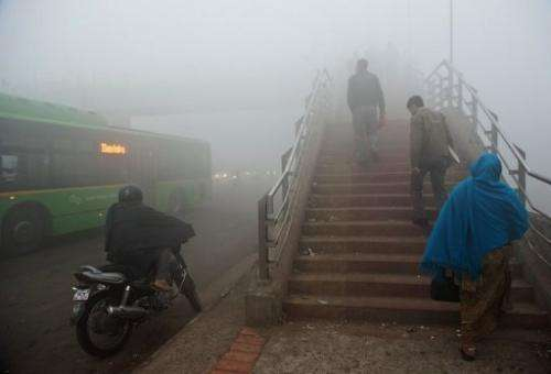 Commuters walk up a foot bridge amid smog in New Delhi on January 31, 2013