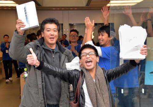 Customers celebrate after buying Apple's new iPad Air tablets at an Apple store in Tokyo on November 1, 2013