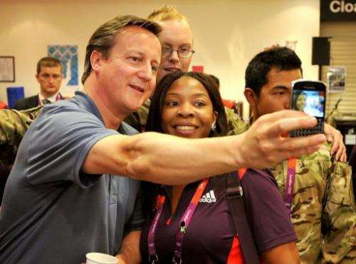 David Cameron takes a selfie picture with with Olympic volunteer Anita Akuwudike in London on August 8, 2012