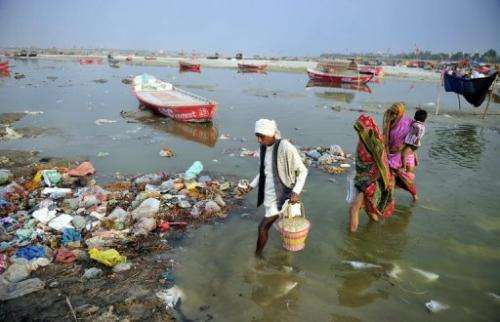 Devotees cross the polluted waters of the Ganga river to take a holy dip at Sangam in Allahabad on April 14, 2013