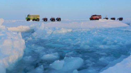 Expedition members use trucks to cross the North Pole