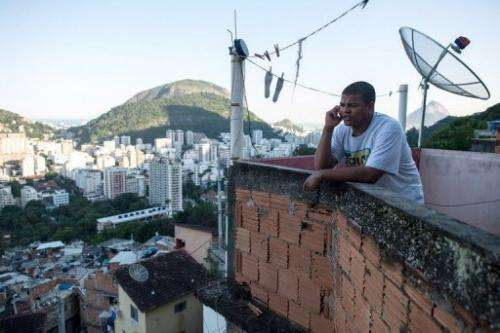 Favela tour guide Thiago Firmino speaks on his cell phone in Santa Marta shantytown in Rio de Janeiro on June 11, 2013