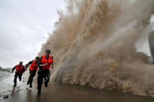 Guards run to escape a wave as Typhoon Fitow makes its landfall in Wenling, east China's Zhejiang province on October 6, 2013