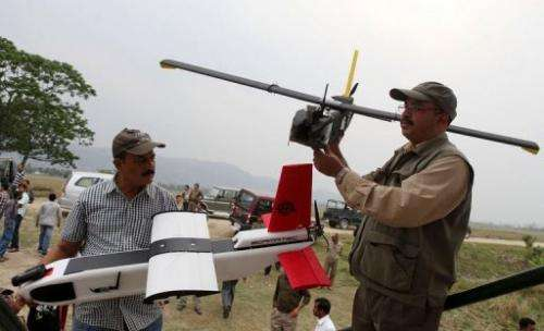 Indian forestry officials hold up unmanned aerial vehicles at the Kaziranga National Park on April 8, 2013