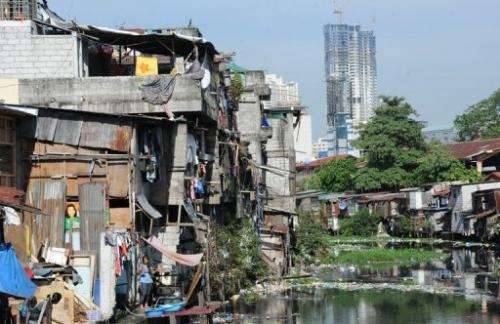 Informal settlers' homes along a waterway in Manila on February 18, 2013