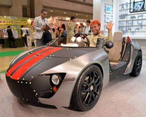 Japanese car designer Kota Nezu poses in a Toyota Motor's concept model, in Tokyo, on June 13, 2013
