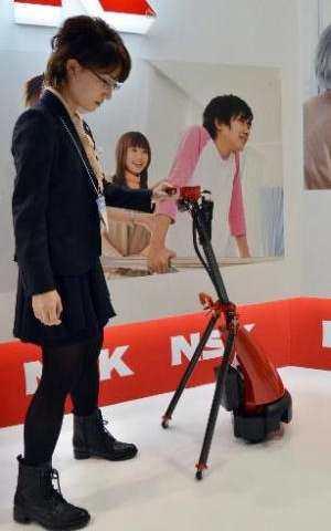 Japan's auto parts maker NSK demonstrates a cane style navigation 'LIGHBOT' robot for elderly and handicaped people, equipped wi