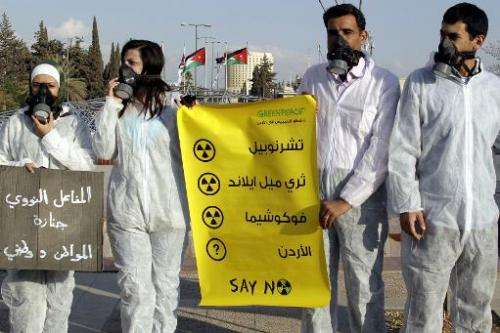Jordanian Greenpeace activists protest outside the premier's office in Amman on October 30, 2011 against the country's official