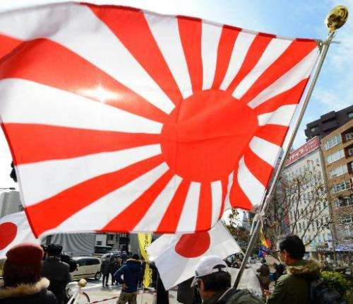"Members of a nationalist group hold a ""Rising Sun"" flag at a rally in Tokyo on February 22, 2013 over the disputed Tak"