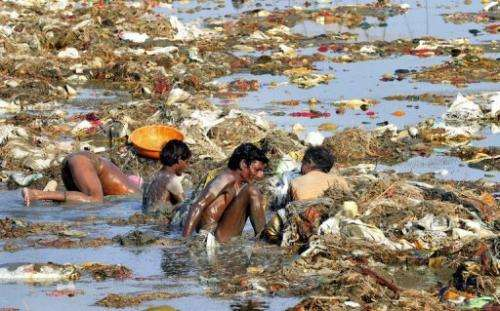 Men hunt coins and gold in the polluted Ganga river at Sangam on April 2, 2013 after the Kumbh Mela festival