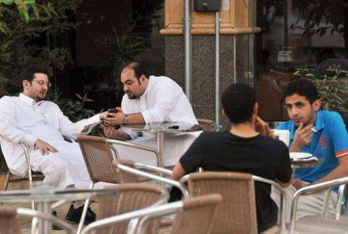 Men look at a mobile as they sit in a coffee shop in the Saudi capital Riyadh on June 17, 2013