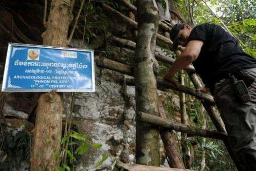Nancy Beavan, an archaeologist who specialises in carbon dating, climbs up a cave at Phnom Pel on March 24, 2013