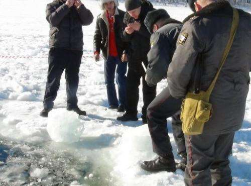 Officers are pictured on February 15, 2013 examining small objects near a hole in a frozen lake outside Chebakul