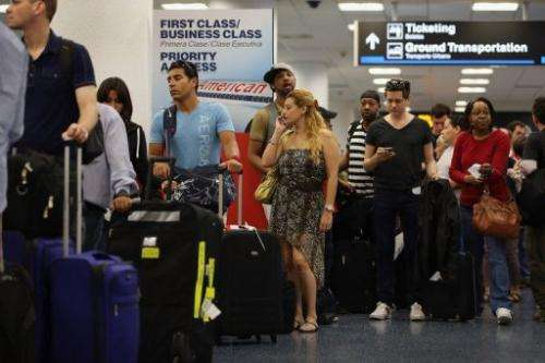 Passengers wait in line for a flight at Miami International Airport on April 16, 2013 in Miami, Florida