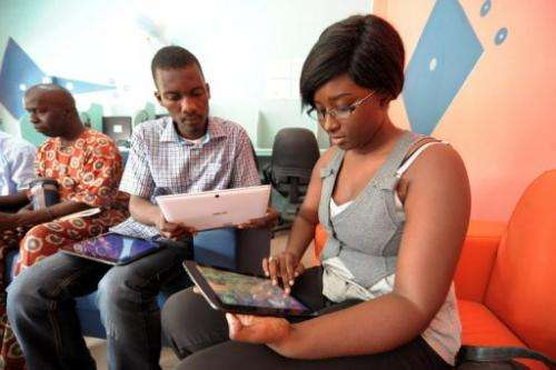 "People browse the Internet using tablets, during the opening of ""Tablette Cafe"", on May 27, 2013, in Dakar"