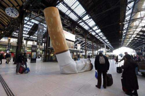 People pass by a giant mock-up discarded cigarette displayed on the ground at the Gare de Lyon railway station in Paris, on Dece