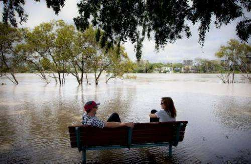 Peter Wilson (left) and Beata Jaremko beside the flooded Brisbane River at West End in Brisbane on January 28, 2013