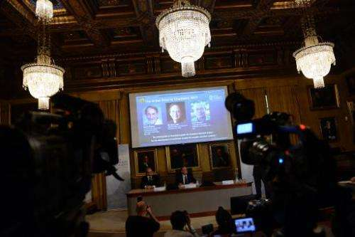 Photos of scientists (L-R) Martin Karplus, Michael Levitt and Arieh Warshel are displayed on a screen at a press conference to a