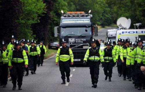 Police personnel escort a lorry to a drill site operated by Cuadrilla Resources in Balcombe,  England, on July 31, 2013