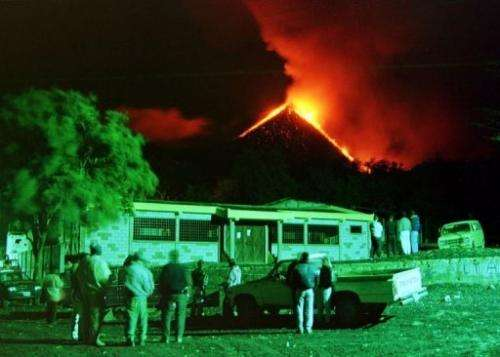 Residents of El Patrocinio watch as a column of fire bursts from the crater of the Pacaya Volcano, on March 1, 2000
