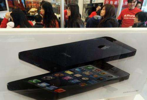 Residents wait in line to purchase the Apple iPhone 5 outside a store in Taipei on December 14, 2012