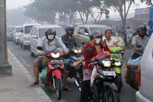 Riders wear masks on a road in Pekabaru, Indonesia's Riau province on Sumatra island on June 21, 2013