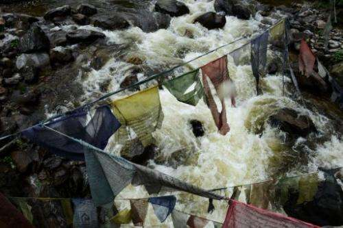 River flows under prayer flags on its way to the Chukha hydropower plant, in south-eastern Bhutan, on May 29, 2013