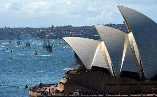Royal Australian Navy warship HMAS Sydney leads the ceremonial fleet in front of Sydney Opera House on October 4, 2013