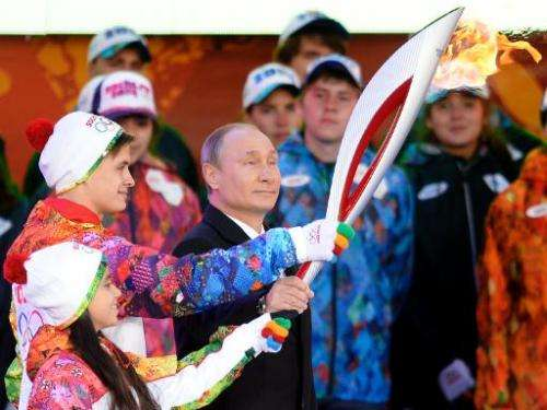 Russian President Vladimir Putin handles a torch in Moscow on October 6, 2013, to start the relay across Russia