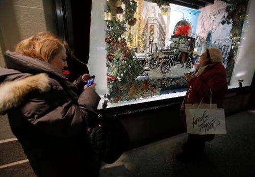 Shoppers admire a holiday window display of the Lord & Taylor Flagship store, in New York, on November 13, 2013