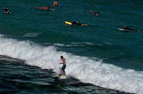 Surfers hit the waves at Bondi beach in Sydney, on January 4, 2013