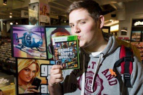 "Taylor Pelling poses with his copy of ""Grand Theft Auto V"" at the HMV music store in central London, September 17, 201"