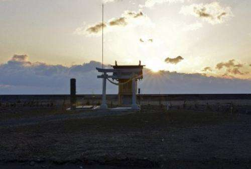 The sun rises behind a shrine to tsunami victims in Minamisoma in Fukushima prefecture on March 11, 2013