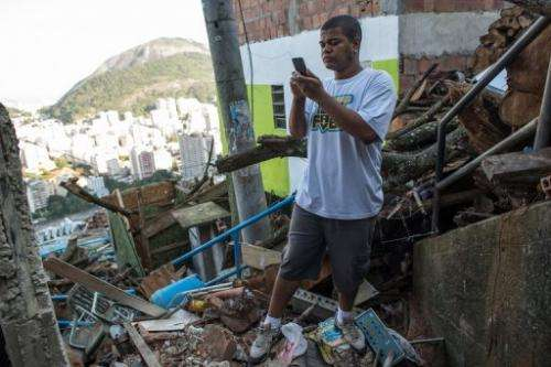 Thiago Firmino takes a picture with his cell phone in Santa Marta shantytown in Rio de Janeiro, Brazil, on June 11, 2013