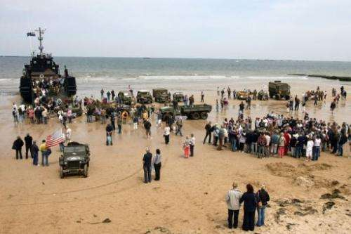 Tourists boarding a landing craft on the beach of Arromanches-les-Bains, northern France on June 6, 2009