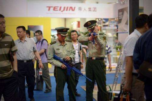Two Chinese paramilitary police test a telescopic sightat a police technology fair in Beijing on May 15, 2013