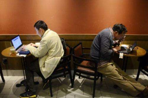 Two men browse the internet on their laptops at a cafe in Beijing on November 2, 2012