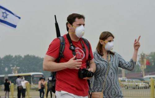 Two tourists wear face masks as they visit Tiananmen Square on a heavily polluted day in Beijing on May 8, 2013