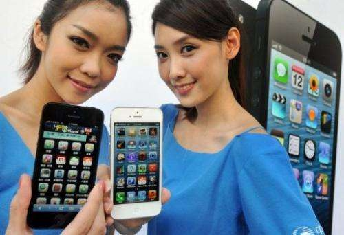 Two women display the Apple iPhone 5 during the product's release at a store in Taipei on December 14, 2012