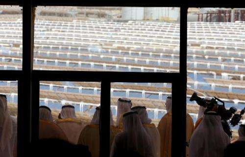 UAE officials look from a balcony at the Shams 1, concentrated solar power plant, in al-Gharibiyah district on the outskirts of