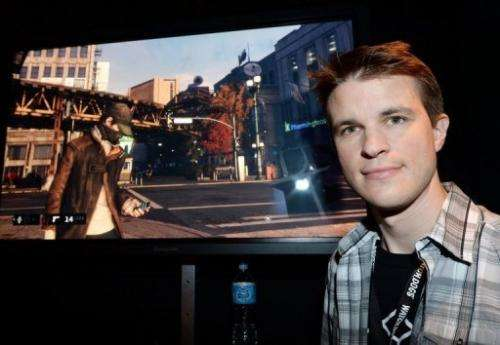 "Ubisoft developer Dominic Guay stands beside a screenshot of ""Watch Dogs"" at the E3 conference in LA on June 12, 2013"