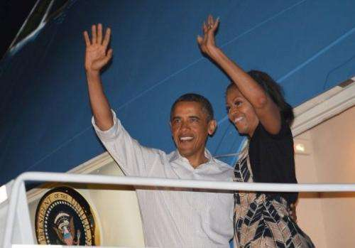 US President Barack Obama and First Lady Michelle Obama (R) wave as they board Air Force One on January 5, 2013