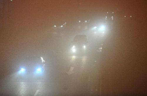 Vehicles move slowly in heavy fog in Hefei, central China's Anhui province on January 14, 2013