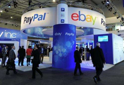Visitors walk past an Ebay and PayPal stand at the Mobile World Congress in Barcelona on February 27, 2013