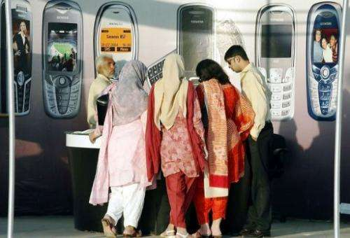 Women visit a stall a mobile phone exhibition in Islamabad on June 19, 2005